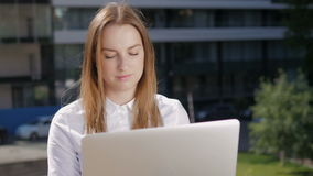 Portrait of Beautiful Business Woman Using Laptop PC Outside Business Center. Portrait of Young Beautiful Business Woman Using Laptop PC Outside Business Center stock footage