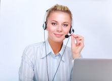 Portrait of beautiful business woman working at her desk with headset and laptop Stock Photos