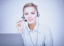Portrait of beautiful business woman working at her desk with headset and laptop Stock Photography