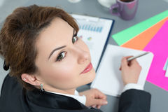 Portrait of beautiful business woman at workplace looking back Stock Photography