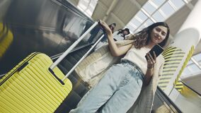 Portrait of beautiful businesslady with suitcase moving down on escalator. Young woman going on business trip, coming to