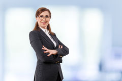 Portrait of a beautiful businesswoman 50 ears old in crossed arms pose in the office. Royalty Free Stock Photo