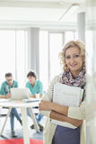 Portrait of beautiful businesswoman holding files with colleagues working in background at creative office Stock Image