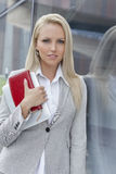 Portrait of beautiful businesswoman holding organizer and digital tablet while leaning on glass wall Stock Photo