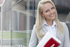 Portrait of beautiful businesswoman with organizer and digital tablet by glass wall Stock Image