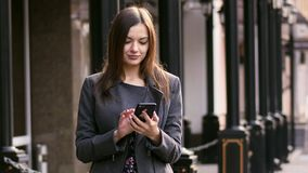 Portrait of beautiful businesswoman on street using smartphone app, surfing internet and smile slow motion. stock video