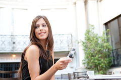 Businesswoman with cell in cafe. Portrait of a beautiful businesswoman using a cell phone while sitting in a classic coffee shop, smiling outdoors Stock Image