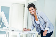 Portrait of beautiful businesswoman writing Stock Photo
