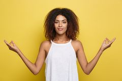 Portrait of beautiful calm young african american black female with Afro hairstyle practicing yoga indoors, meditating. Holding hands in mudra gesture Royalty Free Stock Image