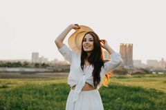 Portrait of beautiful carefree long hair asian girl in white clothes and straw hat enjoys life in field at sunset. Sensitivity to royalty free stock image