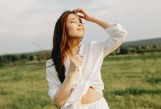 Portrait of beautiful carefree long hair girl in white clothes on field at sunset. Sensitivity to nature concept stock photo