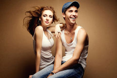 Portrait of a beautiful casual couple in jeans. Sitting together over wooden background. studio shot Royalty Free Stock Photo