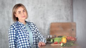 Portrait of beautiful casual girl posing at modern kitchen during cooking medium close-up stock footage
