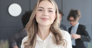 Portrait of beautiful caucasian businesswoman. Smiling with colleagues in the background stock video