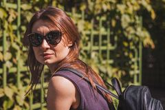 Portrait of a beautiful caucasian girl with brown hair in big sun glasses and with a backpack in travel stock images