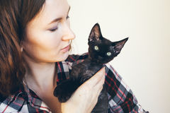 Portrait of a beautiful Caucasian woman with black little kitten. Royalty Free Stock Images