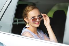 A portrait of beautiful Caucasian woman with blond hair looking through car window to the camera, smiling royalty free stock photo