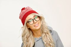 Portrait of beautiful caucasian woman with long blond hair, wears round spectacles, red cap, has a cute smile, isolated stock photo