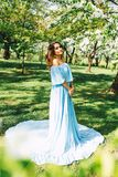 Portrait of beautiful caucasian woman in long dress at the spring blooming garden, long hair and make up, fashion photo stock images