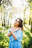 Portrait of beautiful caucasian woman in long dress at the spring blooming garden, long hair and make up, fashion photo royalty free stock image