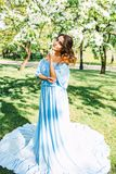 Portrait of beautiful caucasian woman in long dress at the spring blooming garden, long hair and make up, fashion photo Royalty Free Stock Photo