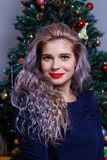 Portrait of a beautiful Caucasian woman posing against the backdrop of the Christmas tree.  stock photo