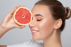 Portrait of a beautiful charming brunette woman with healthy clean skin and fresh make-up. She holds half a grapefruit. Healthy