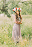 Portrait of beautiful charming young lady in flower wreath and white violet dress looking down Royalty Free Stock Images