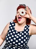 Portrait of beautiful cheerful fat plus size woman pin-up wearing a polka-dot dress isolated over light background, eating a donut royalty free stock photography