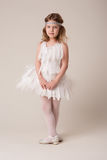 Portrait of a beautiful cheerful girl in a dress of white feathers Stock Image