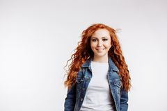 Portrait of beautiful cheerful redhead girl with flying curly hair royalty free stock photography