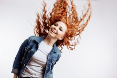Portrait of beautiful cheerful redhead girl with flying curly hair stock photo