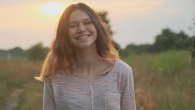 Portrait of beautiful cheerful smiling laughing teenager girl 15 years old, with brown flying hair looking at camera. Nature sunset background stock video