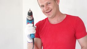 Portrait of a beautiful cheerful young European builder with a drill in his hands.  stock video footage