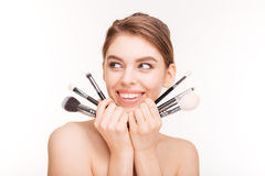 Portrait of beautiful cheerful young woman holding makeup brushes Stock Photo
