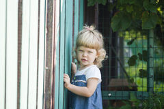 Portrait of the beautiful child with a curly hair about a fence royalty free stock photography