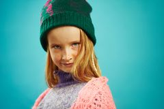Portrait of beautiful child girl in winter sweater and hat on blue isolated. stock photos