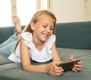 Portrait of a beautiful child lying on the sofa at home smiling. Beautiful cute charming little blonde girl playing and having fun on her smart phone smiling and stock image