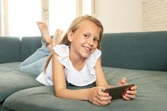 Portrait of a beautiful child lying on the sofa at home smiling and playing with mobile phone. Beautiful cute charming little blonde girl playing and having fun royalty free stock images