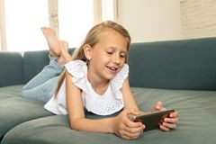 Portrait of a beautiful child lying on the sofa at home smiling and playing with mobile phone. Beautiful cute charming little blonde girl playing and having fun stock image
