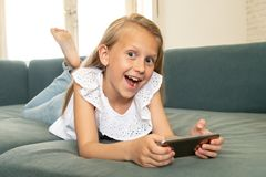 Portrait of a beautiful child lying on the sofa at home smiling and playing with mobile phone. Beautiful cute charming little blonde girl playing and having fun stock photography