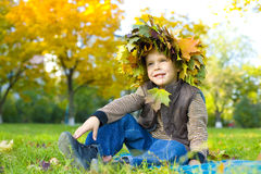 Portrait of beautiful child in wreath from autumn leaves Royalty Free Stock Images
