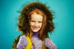 Portrait of beautiful children girl cute smiling, wears autumn warm jacket with fur hood, expresses sincerity, has red royalty free stock images