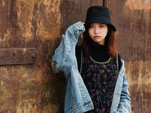 Portrait of a beautiful Chinese girl in blue jeans and black hat posing in front of a rusty door, cute young girl royalty free stock image