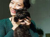 Portrait of beautiful Chinese young girl hug her cute British Shorthair Cat who has amazing orange eyes at home in sunny afternoon royalty free stock photos