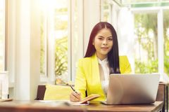 Portrait of beautiful and confident Asian business woman in working with notebook laptop and book manage job work at workplace. Happy businesswoman concept royalty free stock photography
