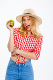 Portrait of beautiful country girl with apple over white background. Stock Photo