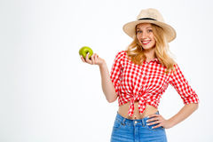 Portrait of beautiful country girl with apple over white background. Royalty Free Stock Image