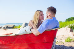 Portrait of beautiful couple in boat on summer beach Stock Image