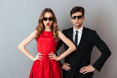 Portrait of a beautiful couple dressed in formal wear. And sunglasses standing and looking at camera over gray wall background Stock Photography